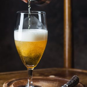 beer pouring into glass from a tin can on dark background